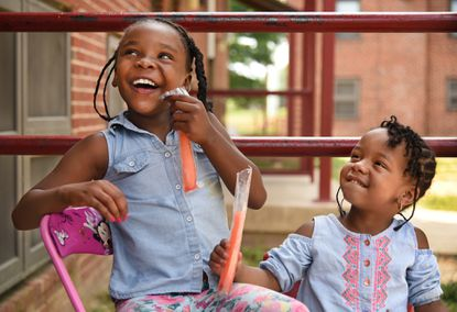 Sisters Chasity Barrett, 8, and Blessin Barrett, 3, enjoy freeze pops as they sit in the shade talking with their grandmother on Slater Road in Cherry Hill.