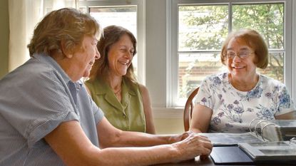 From left, Betsy Lafferty, Jessica Paffenbarger and Carol Hunter laugh around the table in Lafferty's house where they compiled a history of the Towson parade.