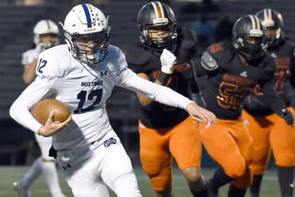 Marriotts Ridge quarterback Casey Pung scrambles for a first down run during a football game at Oakland Mills High School on April 1.