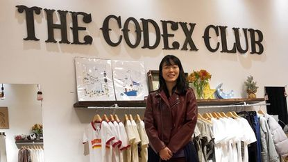 Andrea Chen, owner of The Codex Club, stands before some of the goods crafted by local artisans in her new brick-and-mortar store in Arundel Mills.