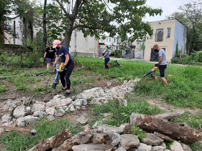 Volunteers from Amazon remove concrete with demolition hammers during a recent workday with The 6th Branch at a vacant lot in the city's Broadway East neighborhood.