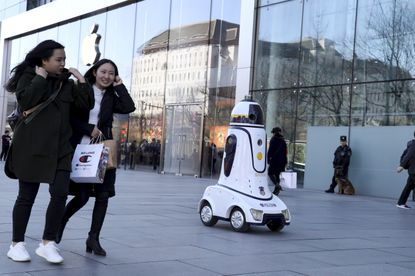 A police robot is stationed near an Apple store in Beijing, China, Wednesday, March 6, 2019. China's emergence as a competitor in key technologies such as smartphones and telecoms equipment has rattled Washington and other governments that worry Chinese competition is a threat to their industries and employment. (AP Photo/Ng Han Guan)