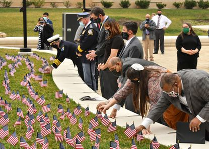 1319 flags at Patriot Plaza in Towson commemorate Baltimore County residents who lost their lives to Covid-19. Baltimore County executive Johnny Olszewski and Health Officer Dr. Gregory Wm. Branch, in front at right, were joined by public safety officials, administrators and faith leaders who all placed flags of remembrance on the one-year anniversary of the first County death due to the pandemic.