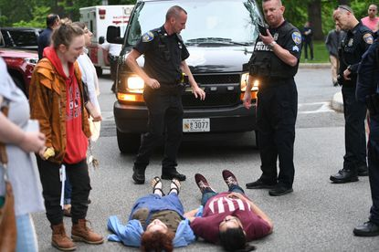 In its push to gain authorization for an armed police force, Johns Hopkins spent more than half a million dollars on lobbying lawmakers in Annapolis this past legislative session. In this file photo, protestors opposed to the forcelie in front of a police van afterthe arrest of several people outside Garland Hall.