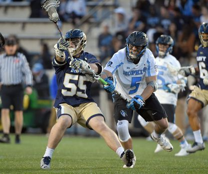 Navy's Brady Dove keeps the ball away from Johns Hopkins' Craig Madarasz in the second half Tuesday night at Homewood Field.