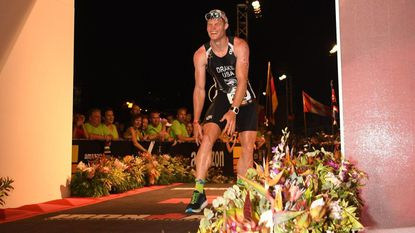 """After a grueling 140.6-mile triathlon that includes a 2.4-mile swim, 112-mile bike and a marathon run, a triumphant Wolfgang """"Wolfie"""" Drake crosses the finish line to become an ironman."""