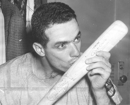 Rocky Colavito of the Cleveland Indians kisses his bat after hitting four home runs in a game against the Orioles at Memorial Stadium in 1959.