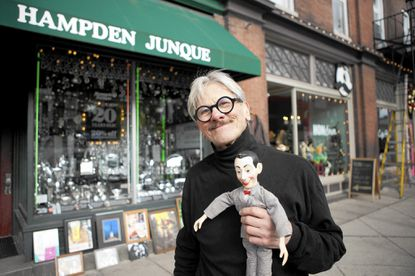 Michal Makarovich poses in front of his store, Hampden Junque, which is celebrating its 20th anniversary, in Hampden.