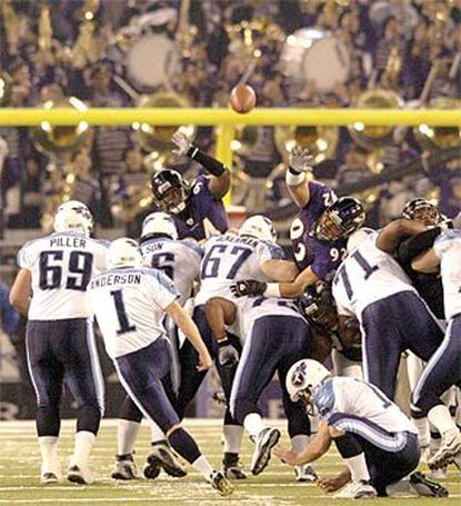 Ravens' Marques Douglas (left) and Maake Kemoeatu (92) rise, but 44-year-old Gary Anderson splits them and the uprights -- just barely -- with his 46-yard field goal in the last minute.