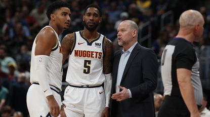 From left, Nuggets guard Gary Harris (14), guard Will Barton (5) and coach Michael Malone talk in the second half of a game Tuesday, March 26, 2019, in Denver.
