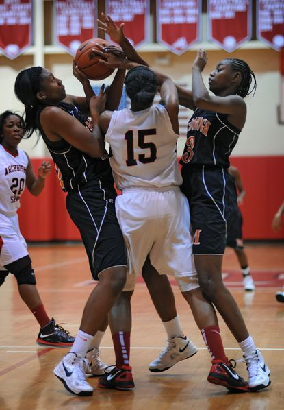 McDonogh's Jameira Johnson, left, and Andrea Robinson team up on Archbishop Spalding's Jade Scaife during the Eagles' 51-32 loss Wednesday night.