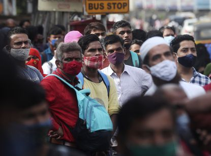 People wearing face masks as a precaution against the coronavirus wait at a bus stop in Mumbai, India, Monday, June 7, 2021. Businesses in two of India's largest cities, New Delhi and Mumbai, are reopening as part of a phased easing of lockdown measures in several states now that the number of new coronavirus infections in the country is on a steady decline. (AP Photo/ Rafiq Maqbool)