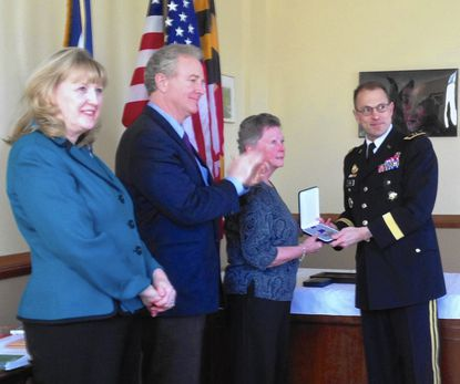 Frederick County Executive Jan Gardner and U.S. Congressman Chris Van Hollen, D-District 8, applaud as U.S. Army Maj. Gen. Brian Lein presents Marie Messner with the Bronze Star earned by her father, James Wivell for his valor as a combat medic in World War II