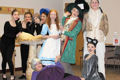 Cast members for Liberty High School¿s production of ¿Alice in Wonderland¿ met up with library patrons ages 2 and older at the Eldersburg branch of Carroll County Public Library Feb. 21. Standing, from left: Mikayla Rodski, Anna Bratsakis, Lily Callahan, Sydney Jones, Delaney Goodwin as Alice, Patrick Owings as the Mad Hatter, and Jordan Spencer as the White Rabbit. Seated, from left: Mickaila Perry as the Caterpillar and Julia Creutzer as the Cheshire Cat. In the scene at the library, Rodski, Bratsakis, Callahan and Jones were working as puppeteers.