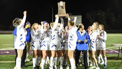Liberty players celebrate with the Class 2A championship trophy following their 1-0 win over Hereford at Washington College on Nov. 10, 2018.