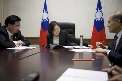 In this photo released by the Taiwanese presidency, President Tsai Ing-wen, center, flanked by National Security Council Secretary-General Joseph Wu, left, and Foreign Minister David Lee, speaks with President-elect Donald Trump through a speaker phone in Taipei.