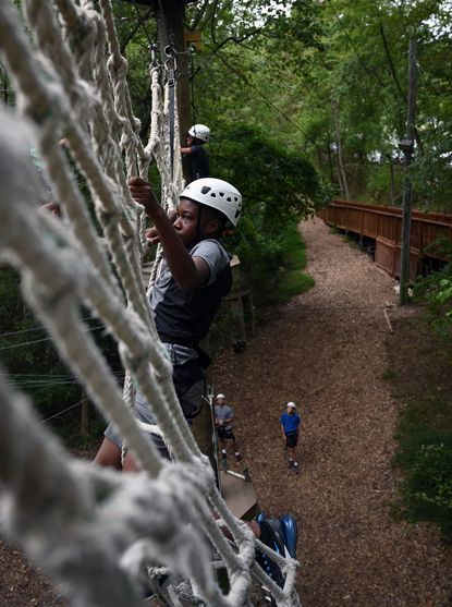 Twelve-year-old Rahman Richardson of Bel Air climbs horizontally on a cargo net at Terrapin Adventures, an aerial adventure park. Richardson and other students from Harford Day School are on the high ropes challenge course.