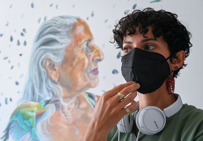In her home on April 27, 2021, artist Jessy DeSantis stands by a painting she created of her grandmother, Vilma Merlo, in late 2019.