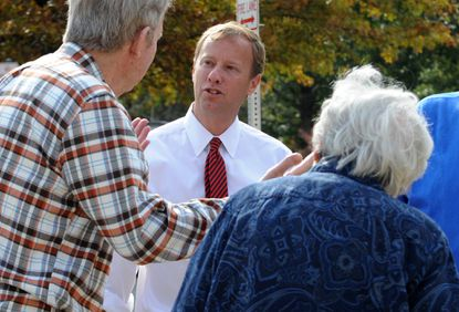 State Senator Jim Brochin speaks with voters Ray and Jean Riordon on their way to the poll at Warren Elementary School where his race is challenged by republican Tim Robinson.