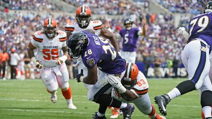 Ravens running back Terrance West drags Browns defensive lineman Trevon Coley for a touchdown in the first quarter at M&T Bank Stadium Sunday.
