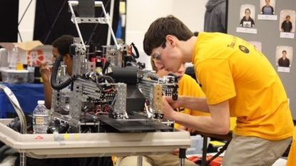 Drew Melis, a senior in his second year with RoboCavs, makes an adjustment to a robot.