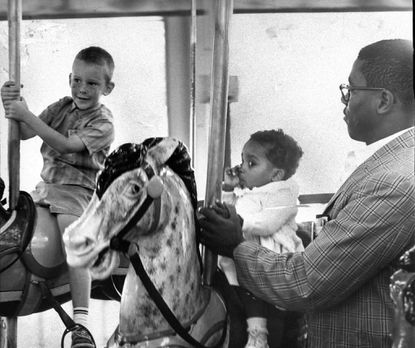 Charles C. Langley Jr. and his daughter, Sharon, 11 months, ride the carousel at Gwynn Oak Park on Aug. 28, 1963.