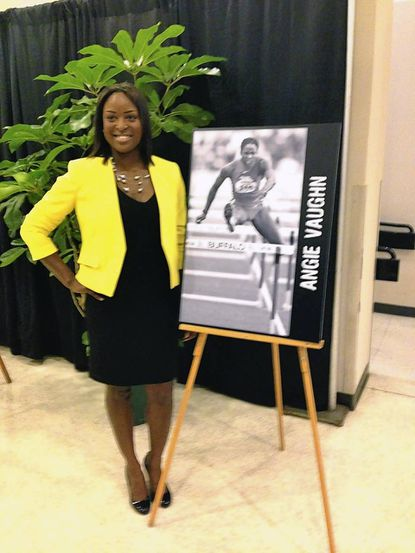 Angie Vaughn poses next to a photo of her hurdling for the University of Texas track and field team. The Laurel High graduate was inducted into the University of Texas Women's Athletic Hall of Fame last fall.