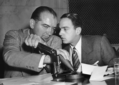 <p>Sen. Joseph McCarthy covers the microphones with his hands while having a whispered discussion with his chief counsel, Roy Cohn, during a committee hearing in Washington in this April 26, 1954 file photo.</p>