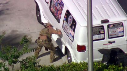 In this still image taken from a video courtesy of television station WPLG, an FBI officer prepares a van to be towed in Plantation, Florida, in connection with the 12 pipe bombs and suspicious packages mailed to top Democrats.