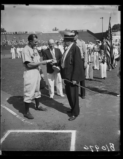 In 1936, Laurel Mayor E.E. Hatch presents a gift to Jake Powell, a racist New York Yankee outfielder. In the background is a contingent of fans and the American Legion junior drum and bugle corps from Laurel. Courtesy photo/Library of Congress