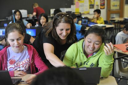 Ellicott Mills Middle School teacher Betsy Adelman, center, works with GT Research student Angela Wang, 11. At left, Libby Milano, 12, works on a computer.