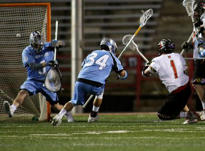 Maryland attackman Matt Rambo (1) fires a shot past Johns Hopkins goalie Eric Schneider (6) and Johns Hopkins Long Stick Midfielder Michael Pellegrino (34) for a goal during an NCAA Men's lacrosse match between the University of Maryland and Johns Hopkins at the University of Maryland in College Park, Maryland.