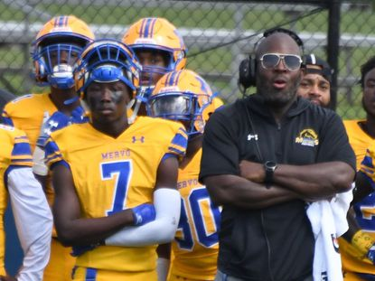 Mervo football player Elijah Gorham, left, stands next to coach Patrick Nixon, right, on the sideline during a game against Dunbar at Baltimore Polytechnic stadium on Sept. 18.