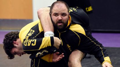 South Carroll Wrestling coach Bryan Hamper uses Jake MacKenzie, since graduated, to demonstrate a wrestling technique to the team in December 2016.