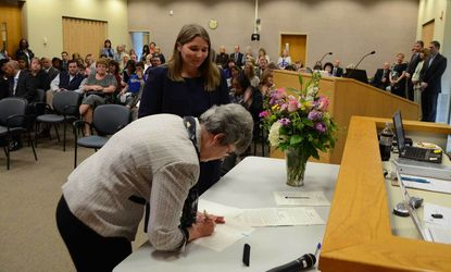 Incoming Superintendent of Schools Renee Foose and Howard County School Board Chairman Sandra French sign Foose's contract before the board's April meeting Thursday.