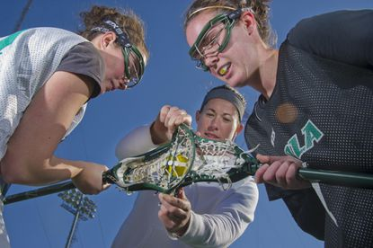 Loyola assistant coach Dana Dobbie (center) places the ball into position for Julie Morse (left) and Casscur Saro, who demonstrate the position of the ball during a draw under new women's college lacrosse rules implemented for this season.