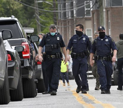Members of the Baltimore County emerge from down the street from the crime scene. Police involved shooting in Baltimore County - resulting in a police chase.