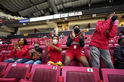 Tierra Haynes, left, wife of Maryland assistant coach DeAndre Haynes, not visible, cheers while sitting with their children, from left, Dallas Haynes, 6, Devon Haynes, 8, DeAndre Haynes Jr., 13, and the son of assistant coach Bino Ranson, B.J. Ranson, 13, far right, while watching the first half of an NCAA college basketball game against Penn State, Sunday, March 7, 2021, in College Park, Md. The game marked the first time during the regular season that Maryland allowed spectators in the stands because of the Covid-19 pandemic as life is slowly starting to get back to normal. (AP Photo/Julio Cortez)