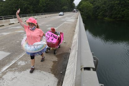 Elizabeth Crutchley waves to passing motorists as she walks along Liberty Road in Eldersburg Tuesday, July 7, 2020 in support of her neice Lindsey Cohen who is battling breast cancer.