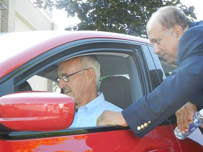 "John Davis, right, shows Doug Miller the interior of a Dodge Dart during a gathering of the Carroll Technology Council outside the Carroll Non-profit Center in Westminster Thursday. Davis, the host of the PBS program ""MotorWeek"" led a discussion of vehicle technology."