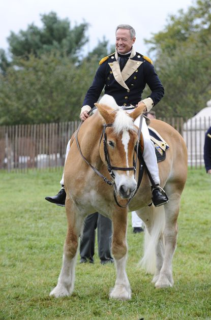 Former Governor Martin O'Malley rides a horse while dressed in a War of 1812 uniform at Fort McHenry.