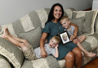 Katelin Krueger, pictured with her sons Zachary, left, and Jacob, both 4, holds a photograph of their brother Aiden Friday, June 18, 2021. Katelin and her husband Tom founded the Krueger Hat Trick Foundation to support families who have children with congenital heart ailments after they lost Aiden in October, 2019.