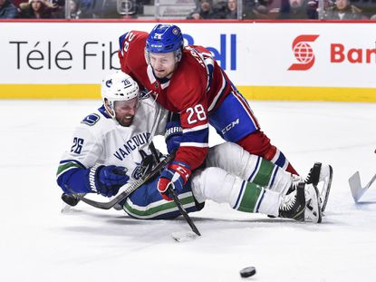 Jakub Jerabek of the Montreal Canadiens takes down Thomas Vanek of the Vancouver Canucks during a game at the Bell Centre on January 7, 2018 in Montreal.