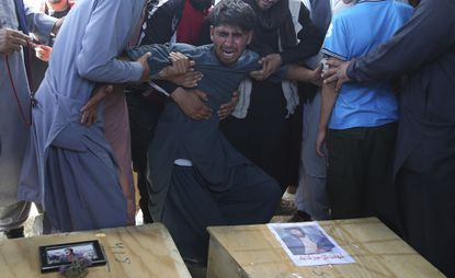 A relative wails near the coffins of victims of the Dubai City wedding hall bombing during a mass funeral in Kabul, Afghanistan, on Aug.18, 2019.