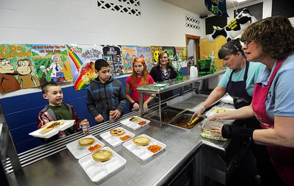 Trinka Palmer, right, and Debbie Siegman serve, from left, fifth-graders Jack Sloan, Nathan Gelsinger, Destiny Haney and special education assistant Joanne Bowen during lunch at William Winchester Elementary School in Westminster Thursday.