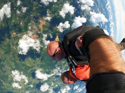 In photo taken by instructor Darren Lewis, comic Michael Aronin, in brightly colored shirt, free falls during his tandem jump over Harford County in August.