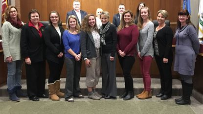 Six women who were nursing students at Harford Community College last semester and went to Estonia to teach HIV prevention, posed for a group photo with their advisors and Bel Air's Board of Town Commissioners, following a presentation about the trip Tuesday night at Town Hall.