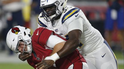 Chargers defensive tackle Corey Liuget (94) grabs the face mask of Arizona Cardinals quarterback Josh Rosen (3) for a 15-yard penalty during the first half of a preseason game on Aug. 11 in Glendale, Ariz.