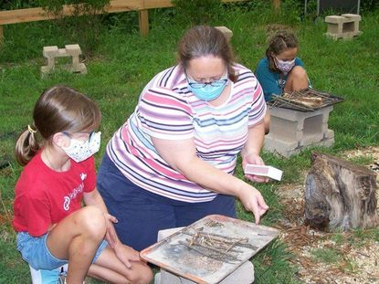 Gretchen Magno, a leader in American Heritage Girls Troop MD1208, helps member Eva Grace Sullivan work on fire safety and fire building during the group's Twilight Camp in July.