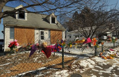 At the parsonage of the Sinnah family, flowers and other tributes adorn the fence and entrance, after the fatal fire that took three lives.